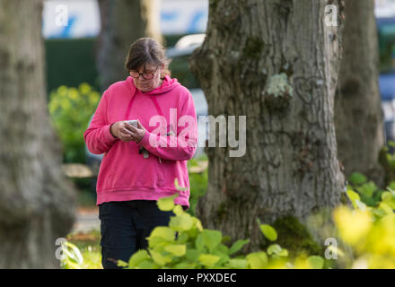 Middle aged woman looking down typing on smartphone while walking, in the UK. - Stock Photo