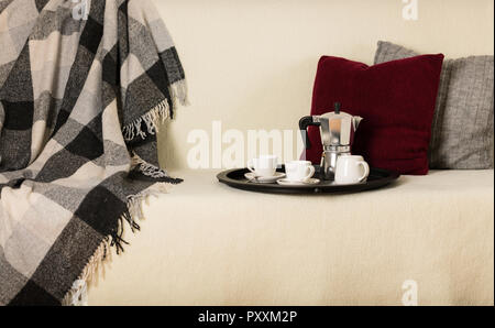 Round black metal tray with a coffee maker and a cup on a white sofa with a gray plaid and pillows. Selective focus. - Stock Photo