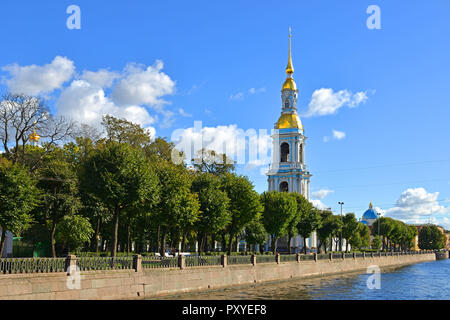 Four story bell tower with tall gilded spire (1755–1758) of St. Nicholas Cathedral and garden. Saint Petersburg, Russia - Stock Photo