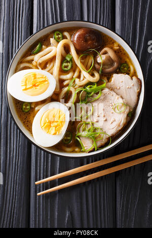 Asian style soup with udon noodles, pork, boiled eggs, mushrooms and green onions close-up in a bowl on the table. Vertical top view from above - Stock Photo