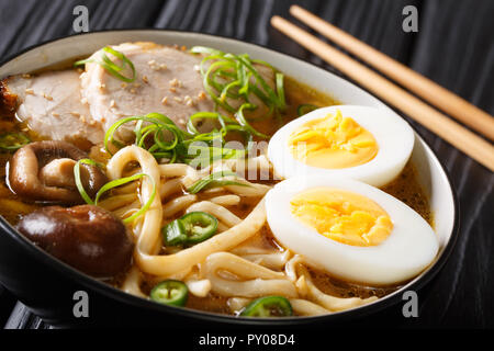 Spicy udon noodle soup, pork, boiled eggs, shiitake and onions close-up in a bowl on the table. horizontal - Stock Photo