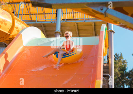 A young woman came down from the water slide on a rubber circle with a camera in her hand. - Stock Photo