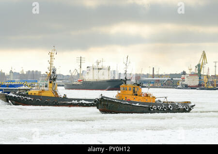 The boat works in the port.He pulls a tanker from the berth after loading. - Stock Photo
