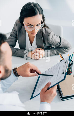 doctor pointing on insurance claim form to serious patient in clinic - Stock Photo