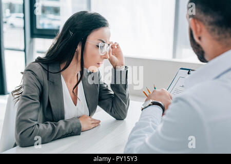 doctor pointing on insurance claim form to female patient in clinic - Stock Photo