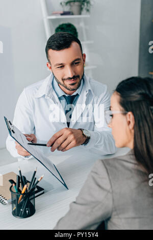 cheerful doctor pointing on insurance claim form to patient in clinic - Stock Photo