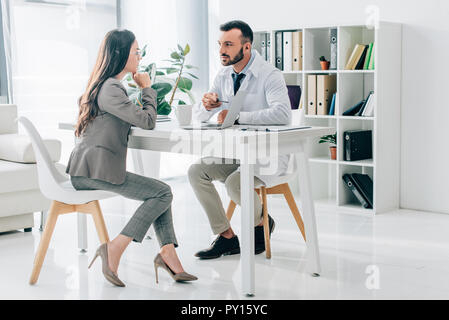 doctor pointing on laptop to patient in clinic - Stock Photo