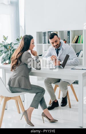 general practitioner pointing on laptop to patient in clinic - Stock Photo