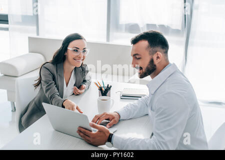 smiling patient pointing on laptop to doctor in clinic - Stock Photo