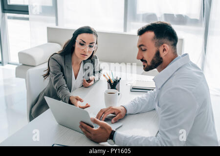 patient pointing on laptop to general practitioner in clinic - Stock Photo