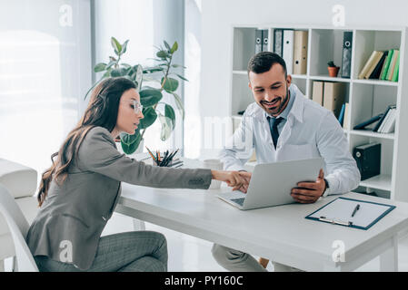 side view of patient pointing on laptop to doctor in clinic - Stock Photo