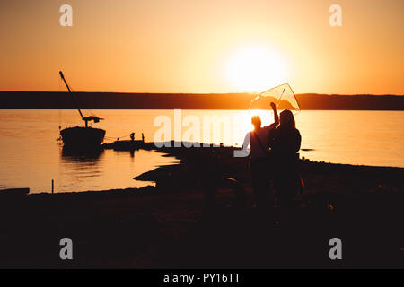 A young couple on the shore launches a kite - Stock Photo