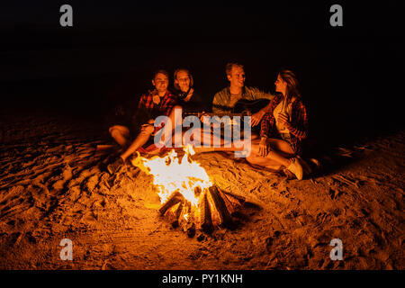 young friends have picnic with bonfire on the beach - Stock Photo