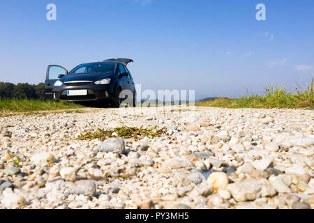 Black van parked on gravel road, low angle, copyspace, trunk and door open, nobody, offroad, camping in nature, plain blue sky in background - Stock Photo