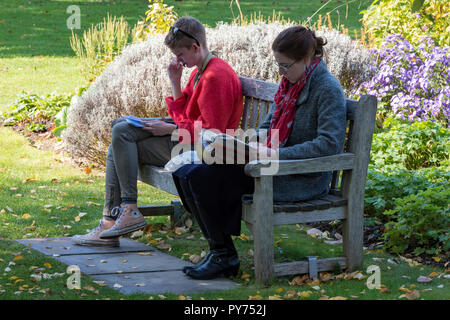 two young ladies or women students sitting or seated on a wooden bench in the bishop's garden at Chichester cathedral in west sussex reading books. - Stock Photo