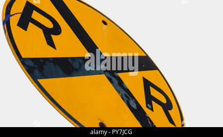 Abstract dirty dingy railroad crossing sign close up with a white sky - Stock Photo