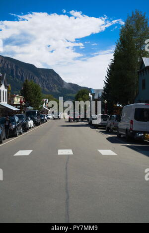 Main Street of Crested Butte Colorado. There is a crosswalk, people, cars parked on the side, trees, buildings, and a blue sky. - Stock Photo