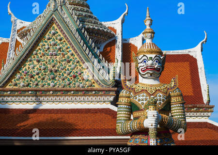 A demonic looking yak or yaksha stands guard at a side building of Wat Arun, or Temple of Dawn, in Bangkok, Thailand - Stock Photo
