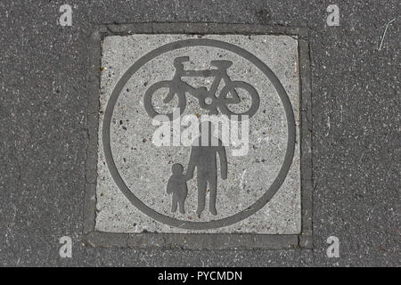 Path Sign For Cycling And Pedestrians.  A signal embedded in asphalt marking a bike and pedestrian route in the park. - Stock Photo
