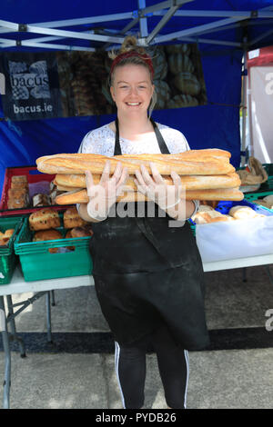 young girl holding long shaped loaves of bread country market, tralee, county kerry, ireland - Stock Photo