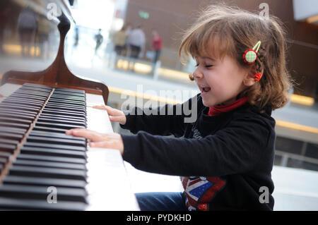 Adorable little girl having fun playing the piano - Stock Photo