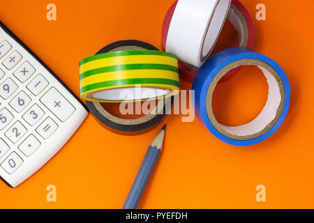 Calculator, insulating tape and pencil on an orange background - Stock Photo