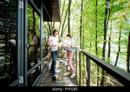 Young creative couple of architechts or designers working with house model and blueprints on the balcony of their office in the forest. Wide view - Stock Photo