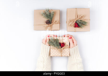 Woman's hands and three vintage minimalistic Christmas gift boxes, decorated with pine cones, pine branches and red berries - Stock Photo