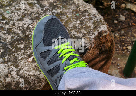 Male shoelaces on a running sneaker, close up. Part of sportsman sneakers. Lower part of a leg on a rock. Men's sportswear, Athlete's foot, - Stock Photo