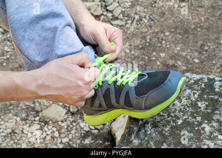 Male hands tying up shoelaces on a running sneaker, close up. Part of sportsman tying sneakers. Leg on a rock. Men's sportswear, Athlete's foot, - Stock Photo