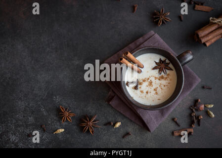 Traditional indian masala chai tea in ceramic cup with ingredients. Spicy black tea with milk on rustic dark background, copy space - Stock Photo