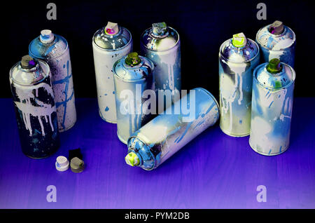 Still life with a large number of used colorful spray cans of aerosol paint lying on the treated wooden surface in the artist's graffiti workshop. Dir - Stock Photo