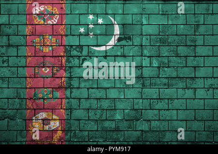 Turkmenistan flag is painted onto an old brick wall - Stock Photo