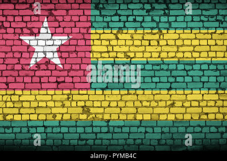 Togo flag is painted onto an old brick wall - Stock Photo