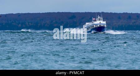 Ferry named Wyandot returning from Mackinac Island to Mackinaw City, Michigan through waves. - Stock Photo