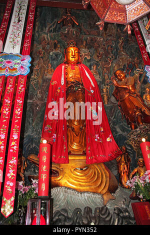 Jade Temple Buddha statue in red robe featuring multicoloured symbols and standing on serpent's head, Shanghai, China - Stock Photo