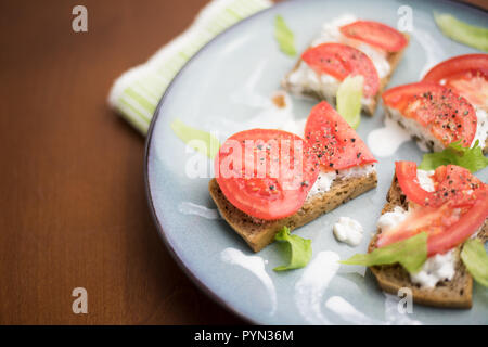 Healthy meal (breakfast, brunch, lunch, supper, dinner) - slice of wholemeal bread with cottage cheese, tomato, basil, lettuce - served on a vintage p - Stock Photo