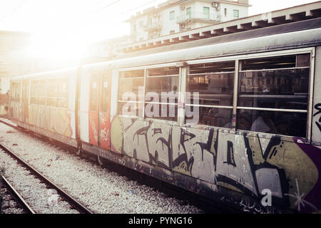 A train with closed doors waiting for passengers at the railway station. Street art and urban culture painted on the tube, Sunlight in background - Stock Photo