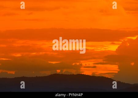sunset in sky and cloud, beautiful colorful twilight time with mountain silhouette - Stock Photo