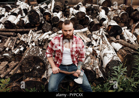 Man sitting on firewoods. Woodcutter with axe resting after work - Stock Photo