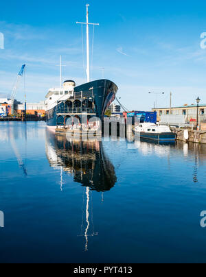 MV Fingal, former lighthouse tender, being converted to luxury 5 star floating hotel in Leith docks, Edinburgh, Scotland, UK with water reflections - Stock Photo