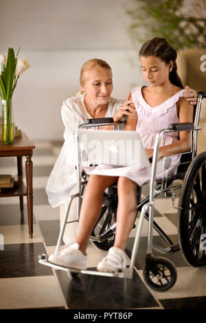Young girl in a wheelchair,  showing something to her grandmother on a laptop. - Stock Photo