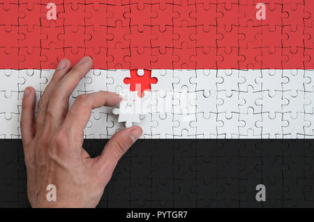 Yemen flag  is depicted on a puzzle, which the man's hand completes to fold. - Stock Photo