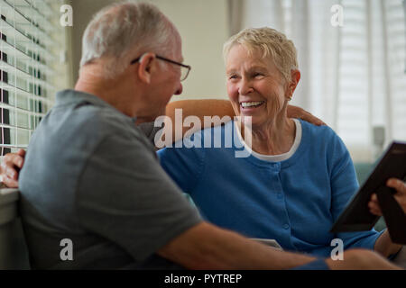 Happy senior couple looking at an old framed photograph. - Stock Photo