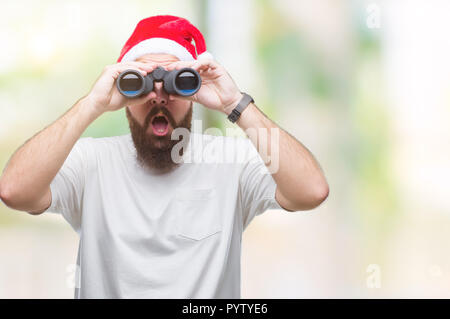 Young caucasian hipster man wearing christmas hat looking though binoculars over isolated background scared in shock with a surprise face, afraid and  - Stock Photo