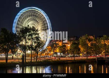 Motion blurred Ferris wheel at night along the Rhone river in the city Avignon, Vaucluse, Provence-Alpes-Côte d'Azur, France - Stock Photo