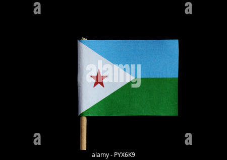 A official national flag of Djibouti on toothpick and black background.  Flag is consist three colours and one red star. - Stock Photo