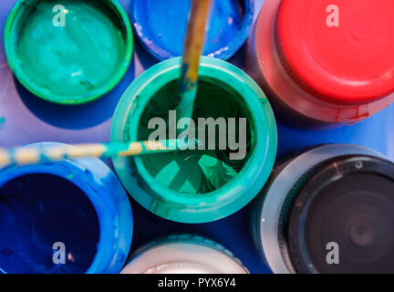 Colorful paint containers that some painter forgot to close - Stock Photo