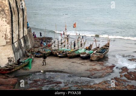 Fishermen and fishing boats at the base of Cape Coast Castle in Cape Coast, Ghana - Stock Photo