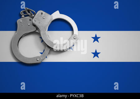 Honduras flag  and police handcuffs. The concept of crime and offenses in the country. - Stock Photo